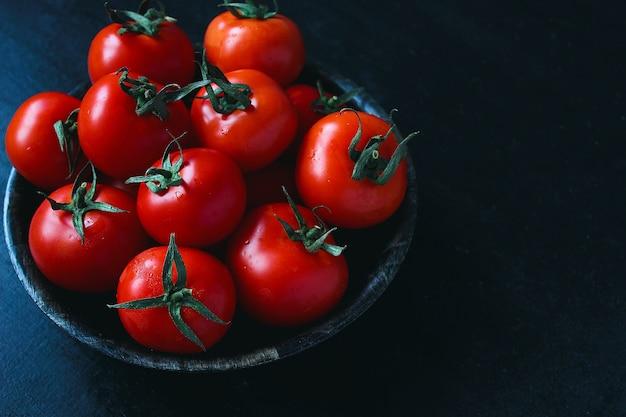 Tomates rouges biologiques fraîches en plaque noire, gros plan, concept santé, vue de dessus
