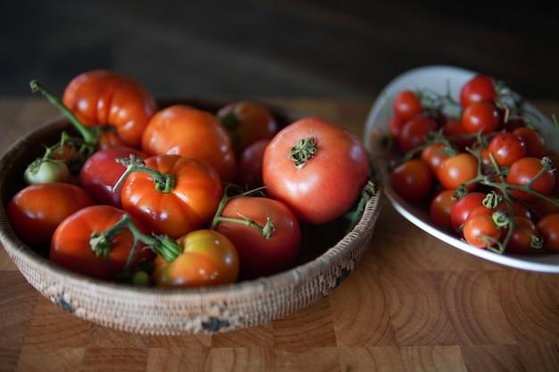 Tomates rouges crues fraîches dans le panier sur la table en bois