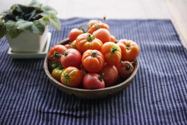 Tomates rouges crues fraîches dans le panier sur la table