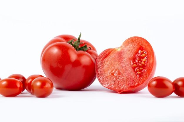 Tomates rouges fraîchement récoltées et tranchées avec des tomates cerises rouges sur un bureau blanc