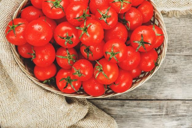 Tomates rouges fraîches dans un panier en osier sur une vieille table en bois. tomates cerises mûres et juteuses avec des gouttes d'humidité, table en bois gris, autour d'un chiffon de toile de jute. dans un style rustique.