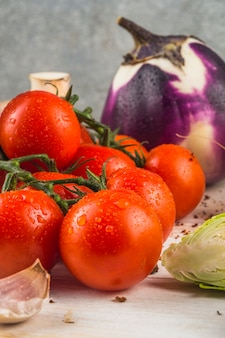 Tomates rouges fraîches; gousse d'ail; choux de bruxelles; aubergine sur une surface en bois
