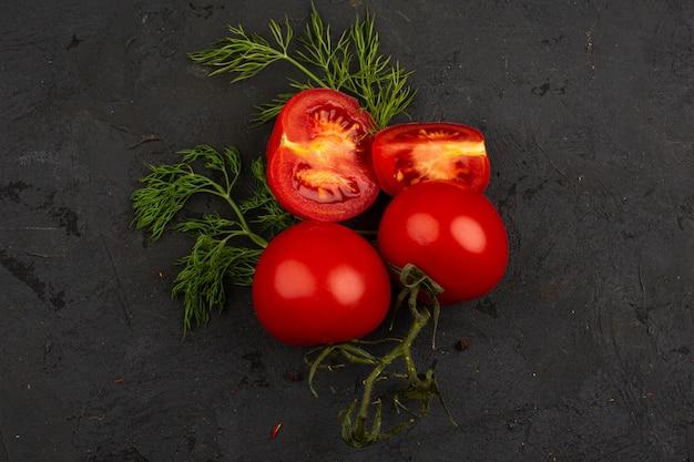 Tomates rouges fraîches mûres tranchées avec des verts sur un bureau gris