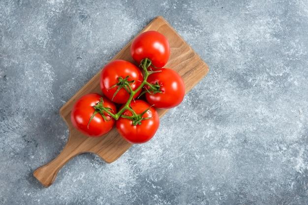 Tomates rouges fraîches sur planche de bois.