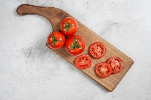 Tomates rouges fraîches sur une planche à découper en bois