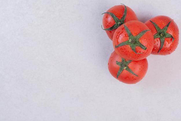 Tomates rouges fraîches sur tableau blanc.