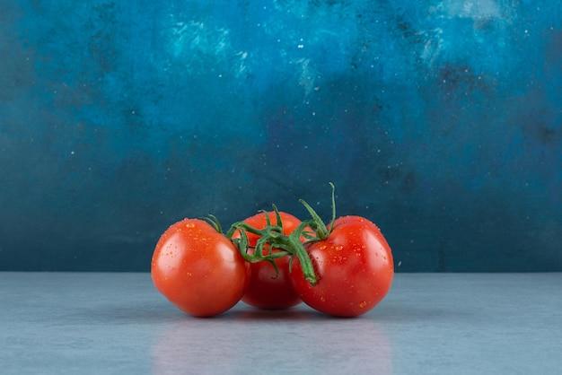 Tomates rouges avec des gouttes d'eau sur bleu.