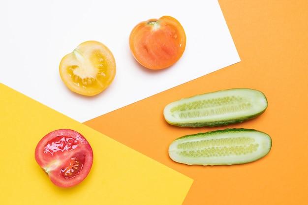 Tomates rouges et jaunes au concombre sur blanc et jaune