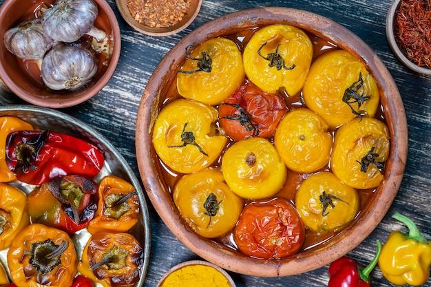 Tomates rouges et jaunes et poivrons au four. tomates et poivrons dans un plat allant au four sur une table en bois. un plat végétarien sain et délicieux. gros plan, vue de dessus