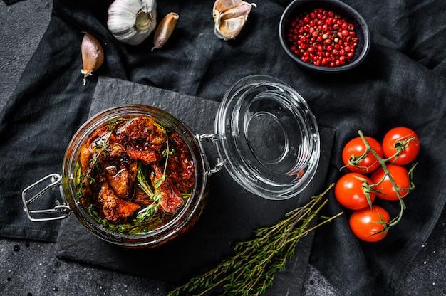 Tomates séchées au soleil aux herbes et sel dans l'huile d'olive dans un verre. vue de dessus