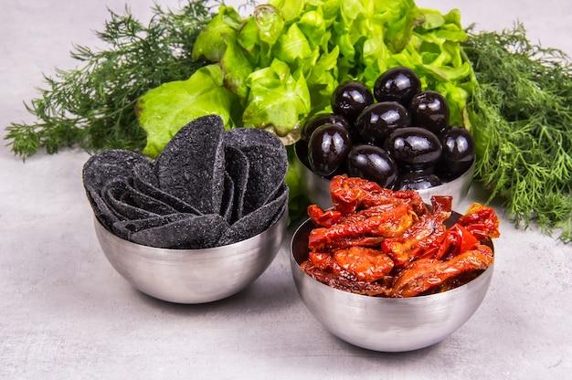 Tomates séchées au soleil, chips noires et olives