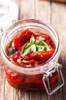 Tomates séchées au soleil dans un bocal en verre avec du basilic frais