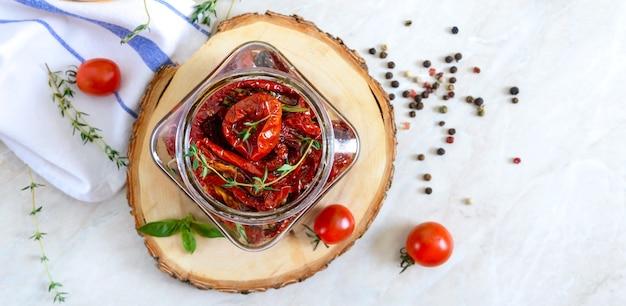 Tomates séchées au soleil avec des herbes à l'ail dans de l'huile d'olive dans un bocal en verre vue de dessus à plat
