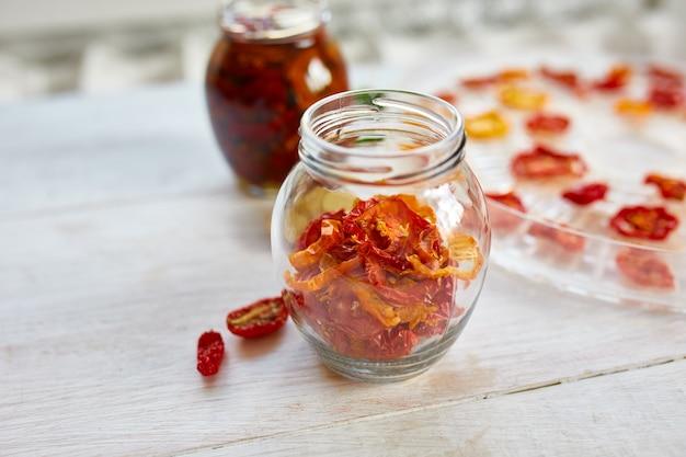 Tomates séchées au soleil maison aux herbes, ail à l'huile d'olive dans un bocal en verre sur fond de bois blanc. copiez l'espace, gros plan. imprimer pour la cuisine.