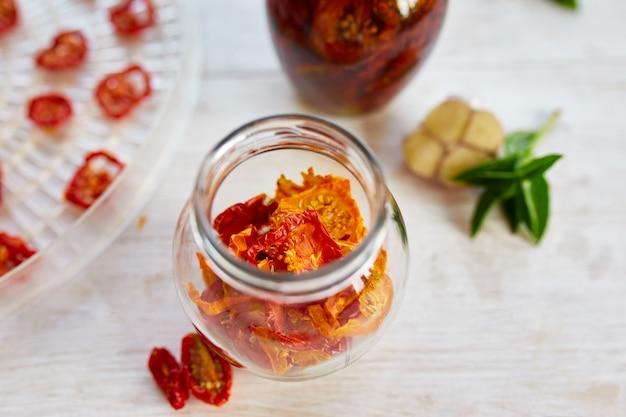 Tomates séchées au soleil maison aux herbes, ail à l'huile d'olive dans un bocal en verre sur fond de bois blanc. vue de dessus. imprimer pour la cuisine