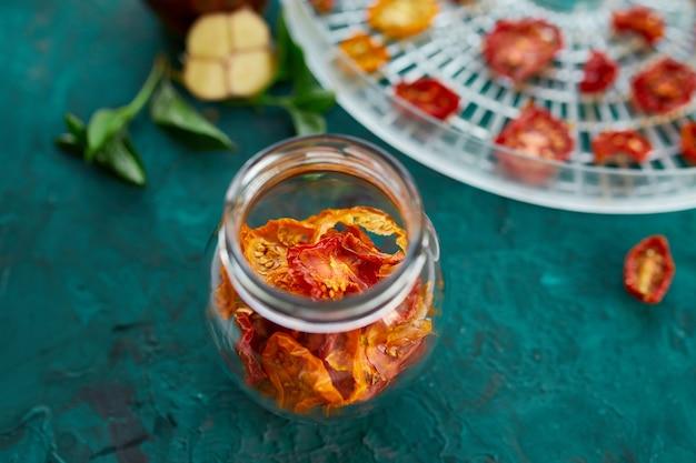Tomates séchées au soleil maison aux herbes, ail à l'huile d'olive dans un bocal en verre