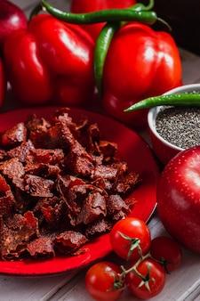 Tomates séchées au soleil avec paprikas et poivrons frais sur plaque rouge