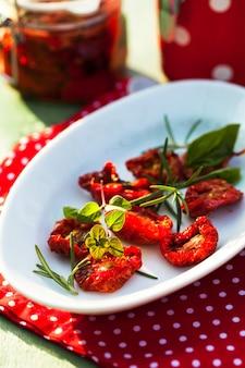 Tomates séchées au soleil sur une plaque blanche avec des herbes fraîches - romarin, basilic et origan