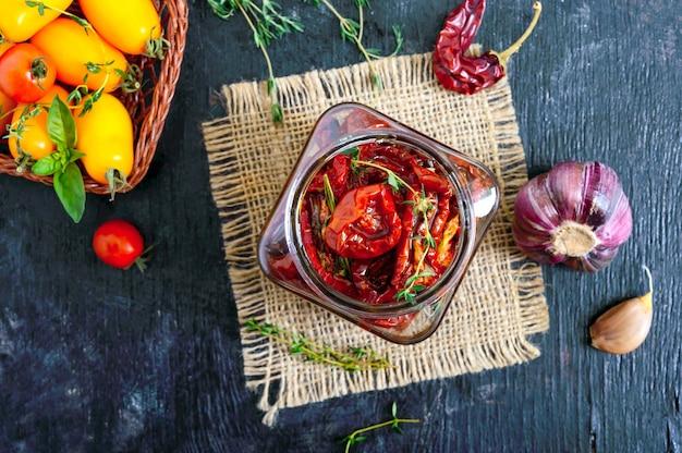 Tomates séchées aux herbes, ail à l'huile d'olive dans un bocal en verre. vue de dessus, mise à plat