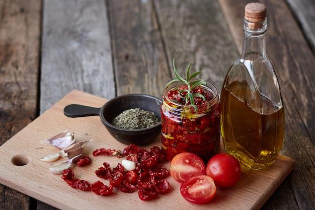 Tomates séchées aux herbes de provence, ail et huile d'olive sur une surface en bois rustique