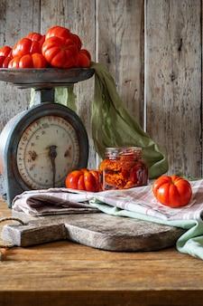 Tomates séchées dans un bocal en verre sur une planche à découper en bois.