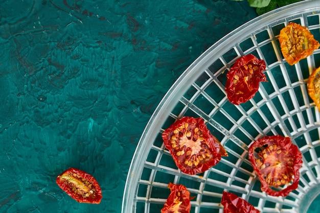 Tomates séchées maison aux herbes, sur le tamis de la sécheuse sur le fond vert. vue de dessus, espace copie, mise à plat