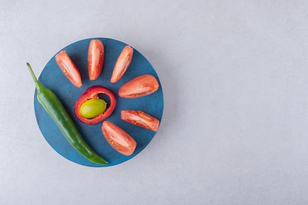 Tomates tranchées et piment sur une assiette sur table en marbre.