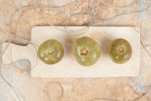 Tomates vertes fermentées sur planche de bois