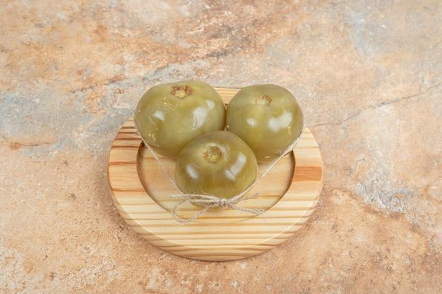 Tomates vertes fermentées sur plaque en bois.