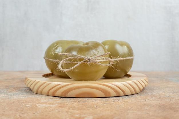 Tomates vertes fermentées sur plaque en bois