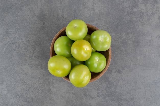 Tomates vertes fraîches dans un bol en bois. photo de haute qualité