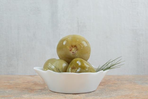 Tomates vertes marinées dans un bol blanc