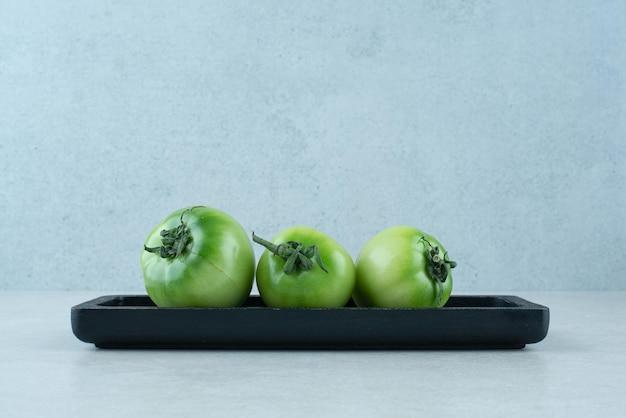 Tomates vertes marinées sur plaque noire.