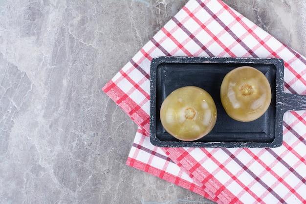 Tomates vertes marinées sur tableau noir