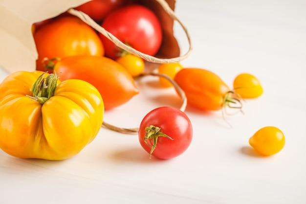Tomates vives dans un sac en papier, fond blanc.