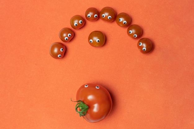 Tomates avec des yeux concept drôle, espace de copie. petite cerise fraîche et grande serre