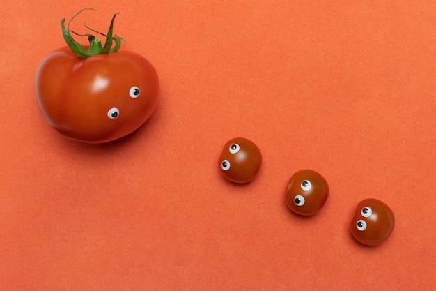 Tomates avec des yeux concept drôle, espace de copie. trois petites cerises fraîches