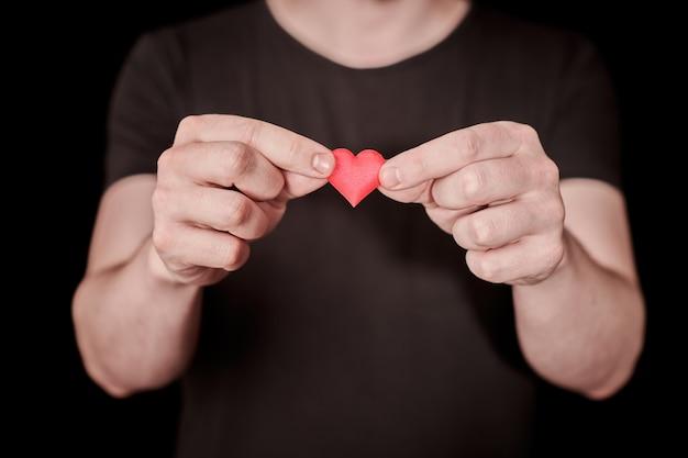 Tomber amoureux du concept. donne un coeur, amoureux mec. coeur comme symbole de l'amour en main. homme solitaire amoureux, tombe amoureux brise-cœur.