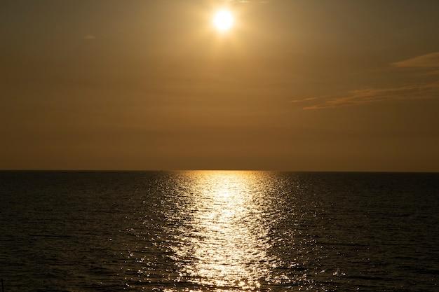 Ton beige argenté coucher de soleil. mer calme avec ciel coucher de soleil et soleil à travers les nuages. méditation océan et fond de ciel. paysage marin tranquille. horizon au-dessus de l'eau.