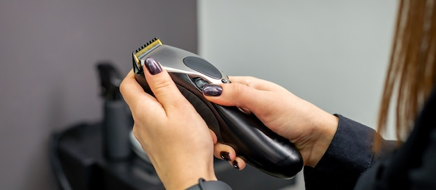 Tondeuse à cheveux dans les mains d'une coiffeuse professionnelle ou d'un coiffeur dans un salon de coiffure