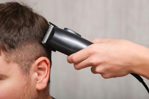 Tondeuse à cheveux en main lors de la coupe.