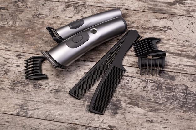 Tondeuse à cheveux avec peigne sur fond de bois