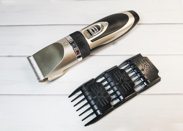 Tondeuse électrique pour animaux de compagnie avec buses en plastique et couteau en céramique sur blanc