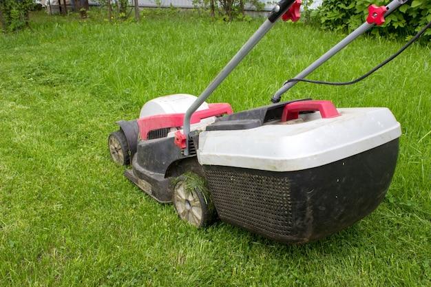 Tondeuse à gazon coupant l'herbe verte dans la cour. tondeuse à gazon sur la pelouse verte fraîche.