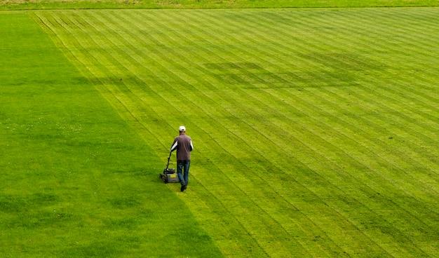 La tondeuse à gazon coupe l'herbe sur le terrain de football tout en travaillant