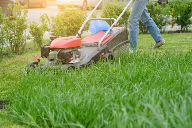 Tondeuse à gazon couper l'herbe verte, jardinier avec tondeuse à gazon de travail