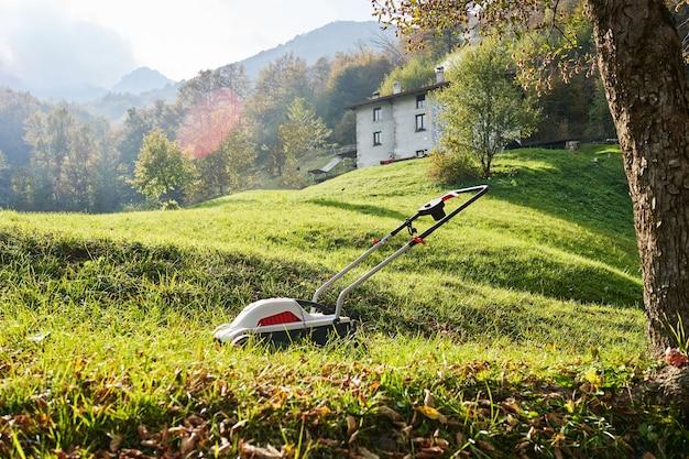 Tondeuse à gazon débroussailleuse sur l'herbe verte dans le jardin en face des montagnes italiennes journée ensoleillée d'automne