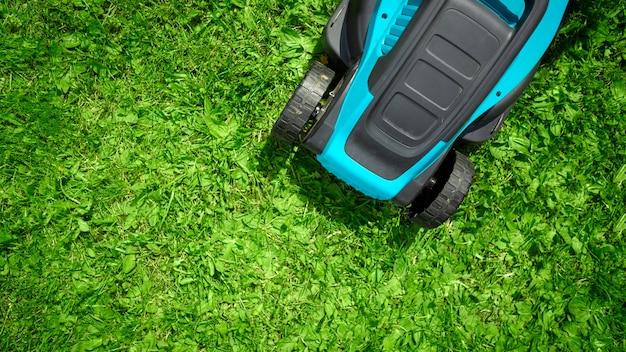Tondeuse à gazon électrique en gros plan, tonte d'herbe, pelouse, chemins. jardinier taillant le jardin
