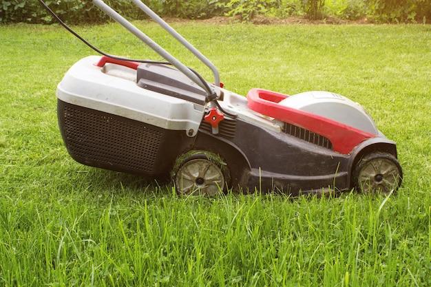 Tondeuse à gazon sur un pré vert. tondeuse à gazon dans le jardin. détails de l'aménagement paysager et du jardinage.