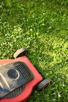 La tondeuse à gazon tond la pelouse dans le jardin de la maison, travaille, lumière du soleil, superbe design pour tous les usages, concept de jardinage